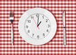 Knife, white plate with clock face and fork on red picnic table - 57027912