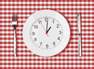 Knife, white plate with clock face and fork on red picnic table
