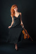 Young woman with violin against black background. Full body port