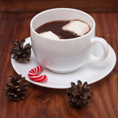White mugs with hot chocolate, marshmallows and Christmas candy