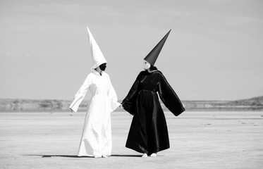 Two people in black cloak and white cloak talking. Artwork