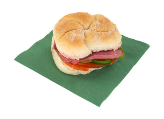 A roast beef bulky roll sandwich on a green napkin