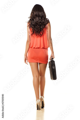rear view of pretty girl in orange dress and laptop bag