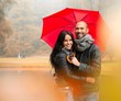 Happy middle-aged couple with umbrella outdoors