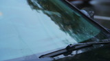 Windscreen wipers on car front glass tearing rain drops, daytime