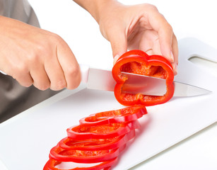 Cook is chopping bell pepper