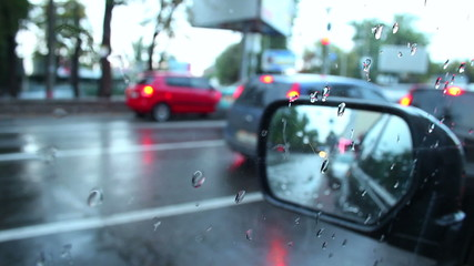 Rear view mirror time lapse, rainy weather, cars pass, stop