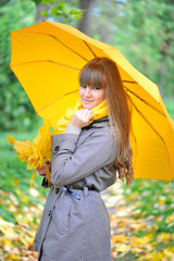 Beautiful young woman is in an autumn park with an umbrella