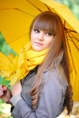 Beautiful young woman with a yellow umbrella