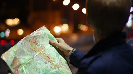Male looking for route in tourist map foreign city night