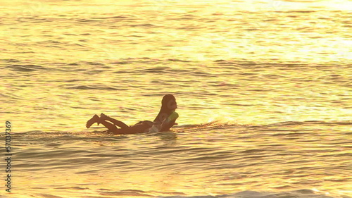 Silhouette Surfer Girl Paddling At Sunset