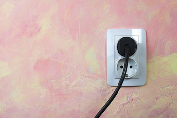 White socket and cable on pink wall.