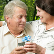 Mature couple embracing in park with gift