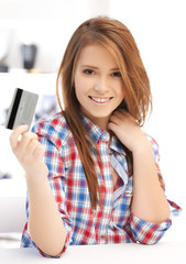 happy teenage girl with credit card