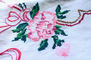 A table-cloth with embroidered rose and decorative ornament