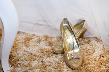 Golden wedding shoes on a carpet
