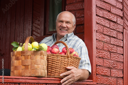 elderly man with   baskets of apples