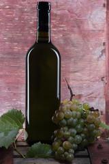 bottiglia di vino bianco con uva bianca su legno