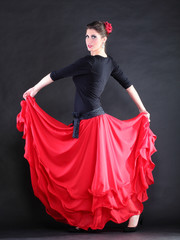 Attractive spanish young woman dancing flamenco over black backg