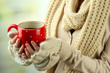 Fototapety Female hands with hot drink, on light background