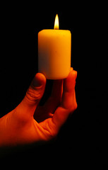 Burning candle in hand isolated on black