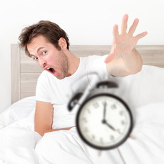 Man waking up late for work early throwing alarm