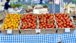 Many ripe tomatoes in totes and marked for sale