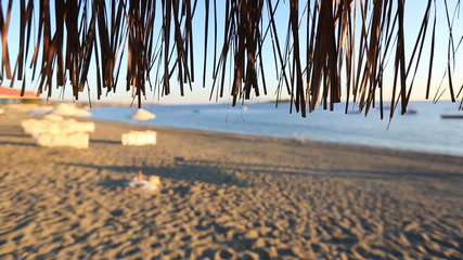 close up beach umbrella waves on sandy beach
