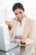 Cheering businesswoman shopping online with laptop