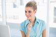 Smiling smart businesswoman looking at laptop