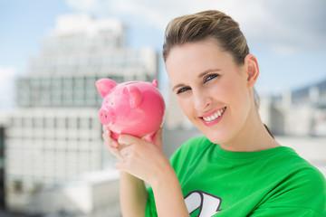 Smiling woman wearing green recycling tshirt holding piggy bank