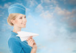 Charming Stewardess Holding Paper Plane In Hand. Blue Sky Backgr