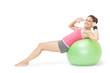 Smiling sporty brunette doing sit ups on exercise ball