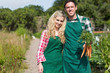 Cute couple posing in their garden holding carrots
