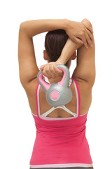 Rear view of sporty brunette holding kettlebell
