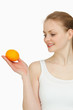 Smiling woman presenting a tangerine while looking at it
