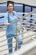 Smiling nurse in a stairwell leaning on the railings