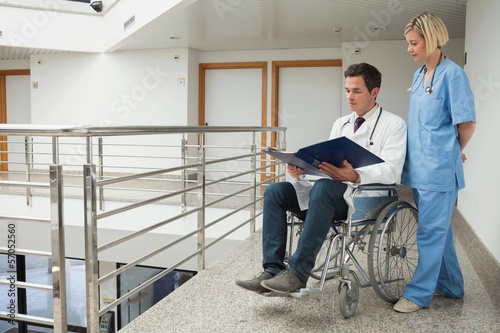Doctor sitting in wheelchair examining notes with nurse