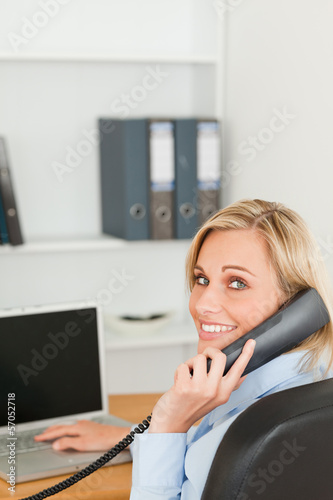 Blonde businesswoman smiling into camera while on the phone