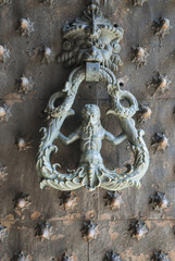 Old door with knocker in the form of mythical figure
