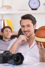 Man holding basketball ball and looking at camera.