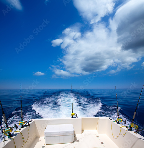 Fishing boat stern deck with trolling fishing rods and reels