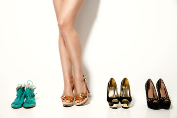Woman's legs and many shoes over white background
