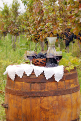 red wine and grape on barrel