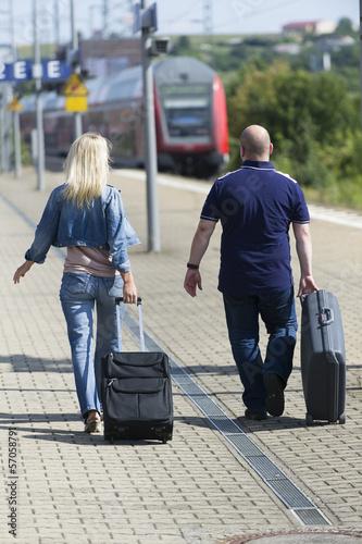 canvas print picture Paar mit Koffer auf dem Bahnsteig