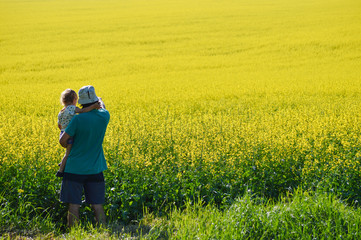 Father and son looking on rapeseed field on summer day
