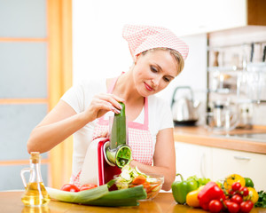 woman cutting vegetables with device at the kitchen table