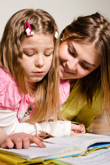 Elder sister teaches to read younger one