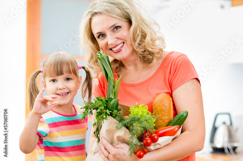 mother and kid holding a shopping bag full of vegetables  on kit