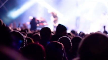De-focused footage of young people dancing at rock concert